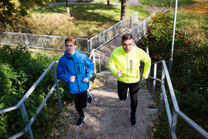 Two young athletes running on stairs outside in colorful sunny autumn nature.Trail runners training for cross country race.