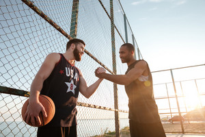 Two young basketball players greeting each other before match at the playground