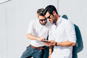 two young bearded blonde and black hair modern businessman, leaning against a wall, using tablet, looking downward the screen - technology, business, work concept