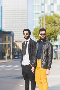 two young bearded blonde and black hair modern businessman, posing in the city, both overlooking - working, successful concept