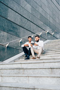 Two young bearded blonde and black hair modern businessman, sitting on a staircase,  using tablet, looking downward the screen - technology, business, work concept