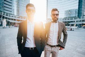 two young bearded blonde and black hair modern businessman, walking in the city backlight, both overlooking right - working, successful concept