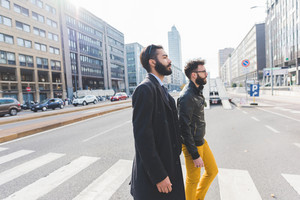 two young bearded blonde and black hair modern businessman, walking in the city backlight, crossing pedestrian crossing - working, successful concept