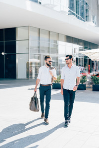 two young bearded blonde and black hair modern businessman, walking in the city backlight,talking together - working, successful concept