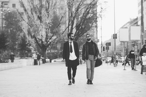 Two young bearded blonde and black hair modern businessman, walking in the city talking to each other - working, successful concept - black and white
