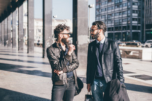 Two young bearded blonde and black hair modern businessman, walking in the city talking to each other- working, successful concept