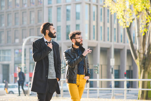 Two young bearded blonde and black hair modern businessman, walking in the city talking to each other - working, successful concept