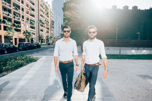 Two young bearded blonde and black hair modern businessman, walking outdoor in the city back light, both looking in camera wearing sunglasses - working, successful concept