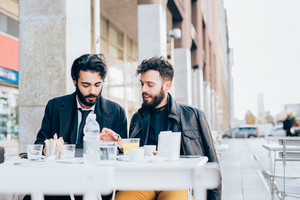 Two young bearded caucasian modern business man sitting in a bar, having breakfast, looking down the screen of a tablet - business, work, technology concept