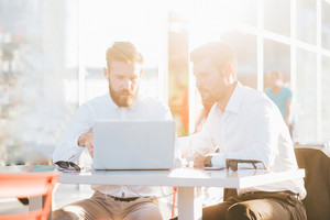 Two young bearded caucasian modern business man sitting in a bar, using laptop, looking downward, tapping on keyboard  - business, work, technology concept - focus on blonde hair man - backlight