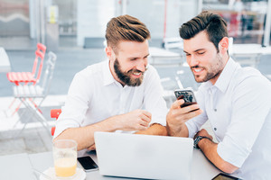 Two young bearded caucasian modern business man sitting in a bar, using laptop,tablet and smart phone - business, work, technology concept
