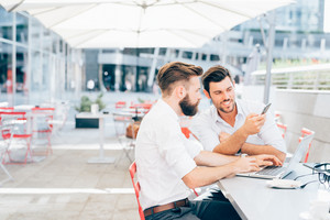 Two young bearded caucasian modern business man sitting in a bar, using smartphone and laptop, looking each other, smiling - business, work, technology concept