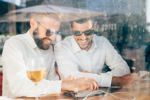 Two young bearded caucasian modern business man sitting in a bar, using tablet looking downward, touching the screen - business, work, technology concept - view behind a shop window