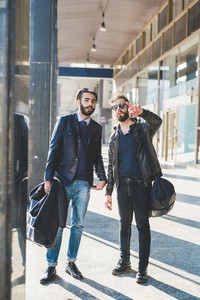 two young bearded contemporary businessman outdoor in the city discussing together - inspiration, planning, project concept