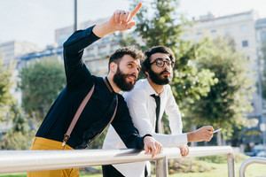 Two young bearded man outdoor discussing pointing at - business, technology, communication concept