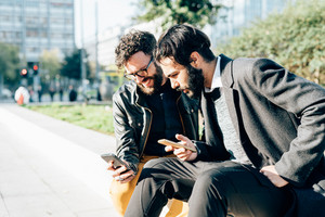Two young bearded man outdoor discussing using smart phone - business, technology, communication concept