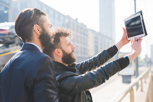 Two young bearded man outdoor in the city holding tablet, taking selfie - social network, technology, friendship concept