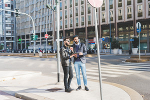 two young bearded modern businessman using tablet handhold outdoor in the city, discussing - technology, business, work concept