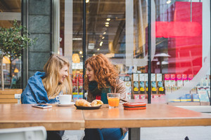 Two young beautiful caucasian blonde and redhead women friends having breakfast outdoor in a bar chatting having fun - friendship, communication concept