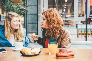 Two young beautiful caucasian blonde and redhead women friends having breakfast outdoor in a bar - friendship, communication concept