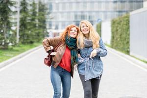 Two young beautiful caucasian blonde and redhead women friends strolling outdoor in the city having fun - friendship, relaxing, having fun concept