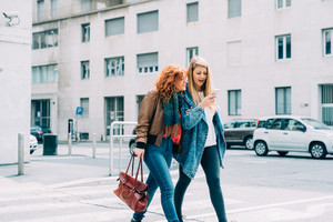 Two young beautiful caucasian blonde and redhead women friends strolling outdoor in the city with smart phone hand hold - friendship, technology, emancipation concept