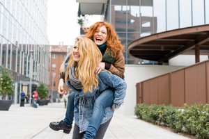 Two young beautiful caucasian blonde and redhead women having fun outdoor in the city riding piggyback - having fun, friendship, carefree concept