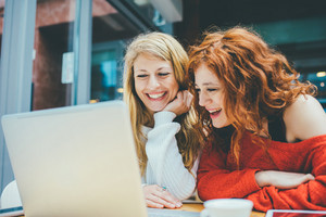 Two young beautiful caucasian blonde and redhead women using computer, looking the screen smiling - student, teamwork, technology concept