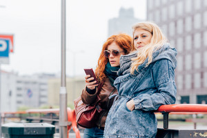 Two young beautiful caucasian blonde and redhead women using smart phone outdoor in the city - technology, social network, communciation concept