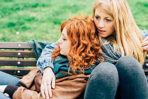 Two young beautiful caucasian redhead and blonde women friends sitting on a bench in a city park, hugging and chatting - friendship, technology, communication concept