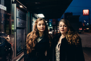 Two young beautiful caucasian women at the bus stop looking in camera - friendship, interaction, commuters concept