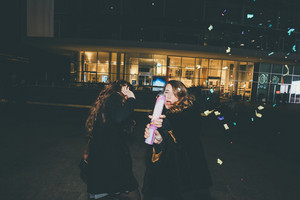 Two young beautiful caucasian women friends outdoor in the city night playing with colorful confetti - celebration, event, party concept
