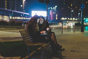 Two young beautiful caucasian women friends outdoor in the city night using computer, tapping keyboard - business, technology, social network concept