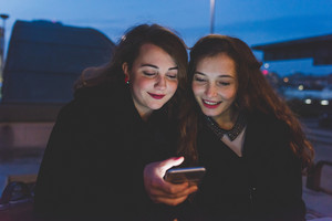 Two young beautiful caucasian women friends outdoor in the city night using smart phone hand hold, face illuminated by screenlight - technology, social network communication concept
