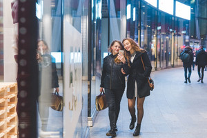 Two young beautiful caucasian women friends outdoor in the city night using smart phone hand hold strolling - technology, social network communication concept