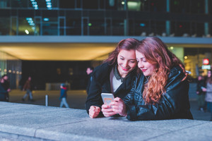 Two young beautiful caucasian women friends outdoor in the city night using smart phone hand hold - technology, social network communication concept