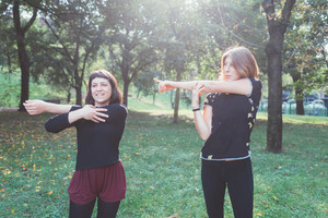Two young beautiful caucasian women stretching outdoor in a city park in sunny day - sportive, training, wellness concept