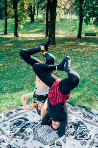 Two young beautiful caucasian women stretching outdoor in a city park in sunny day - sportive, training, yoga concept