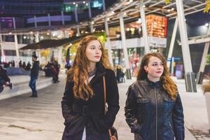 Two young beautiful caucasian women walking outdoor in the city evening, having fun interacting - friendship, interaction, having fun concept