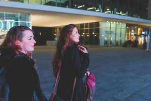 Two young beautiful caucasian women walking outdoor in the city evening, having fun interacting - friendship, interaction, shopping concept
