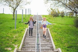 Two young beautiful multiethnic women friends walking down the stairs of a city park, hand in hand, smiling - friendship, emancipation, having fun concept