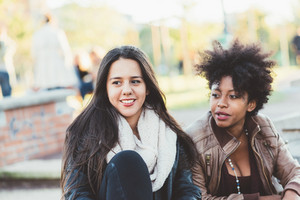 Two young beautiful women friends outdoor in the city chatting - diversity, interaction, gossip conceot