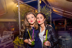 Two young beautiful women in black leather jackets with cocktails in bar or club having fun