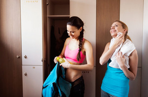 Two young beautiful women in gym changing for workout