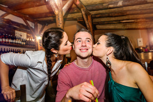 Two young beautiful women kissing man in bar or club having fun