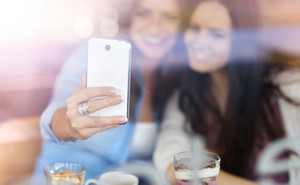 Two young beautiful women with smartphone in cafe