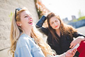 Two young blonde and brunette girls chatting and using technological devices like smartphone and tablet - technology, social network, communication concept