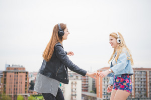 Two young blonde and brunette girls listening to music in the city having fun - music, technology, friendship concept