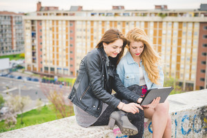 Two young blonde and brunette girls using tablet sitting on a small wall, looking down the screen smiling - technology, social network, communication concept