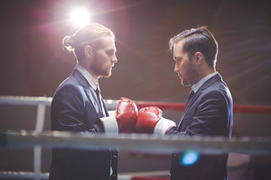 Two young businessmen boxing on boxing ring